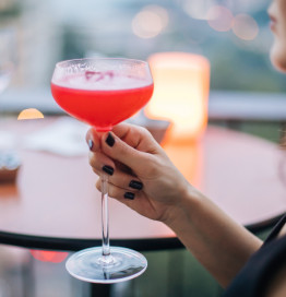 blurry image of woman holding bright red cocktail