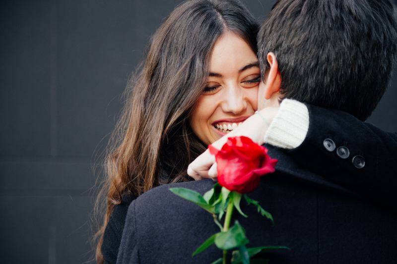 couple hugging female holding red rose