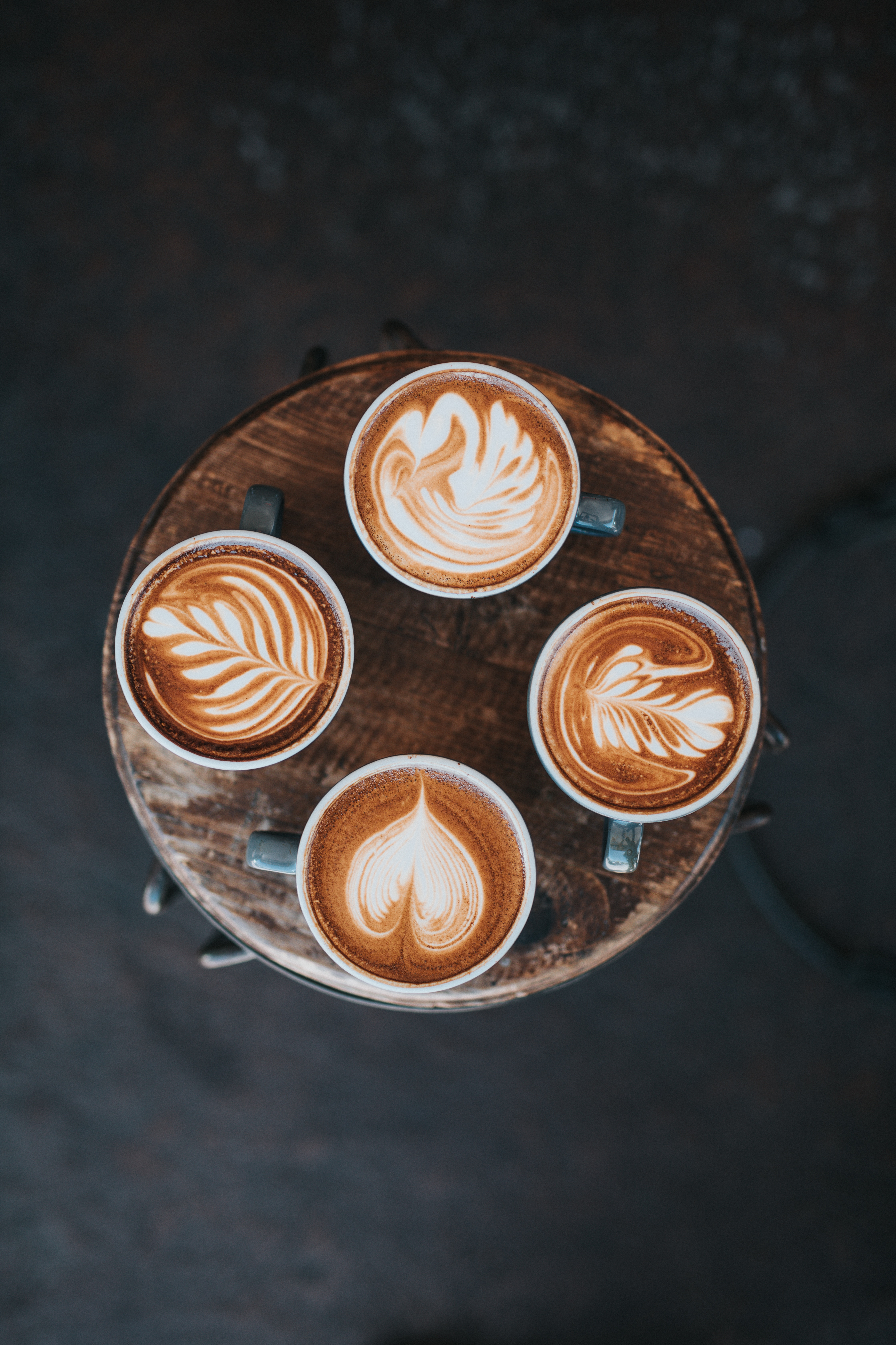 four cappuccinos with different designs in the foam