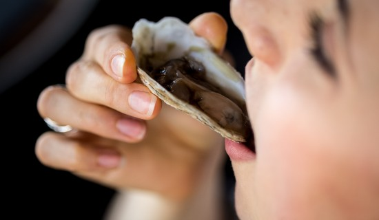 person eating a raw oyster