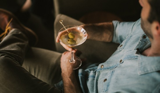 man lounging and drinking a martini with olives
