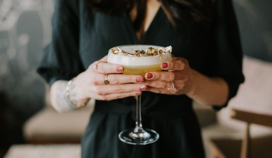 woman with pink nails holding a cocktail