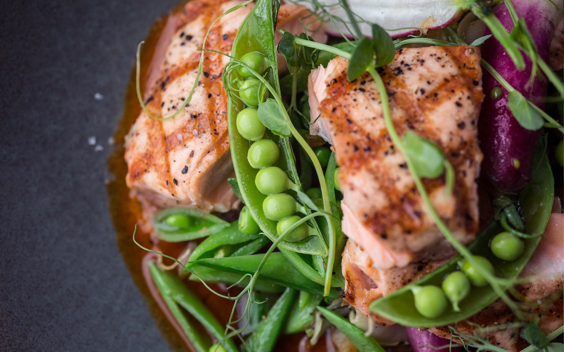 plate of grilled salmon with microgreens and peas