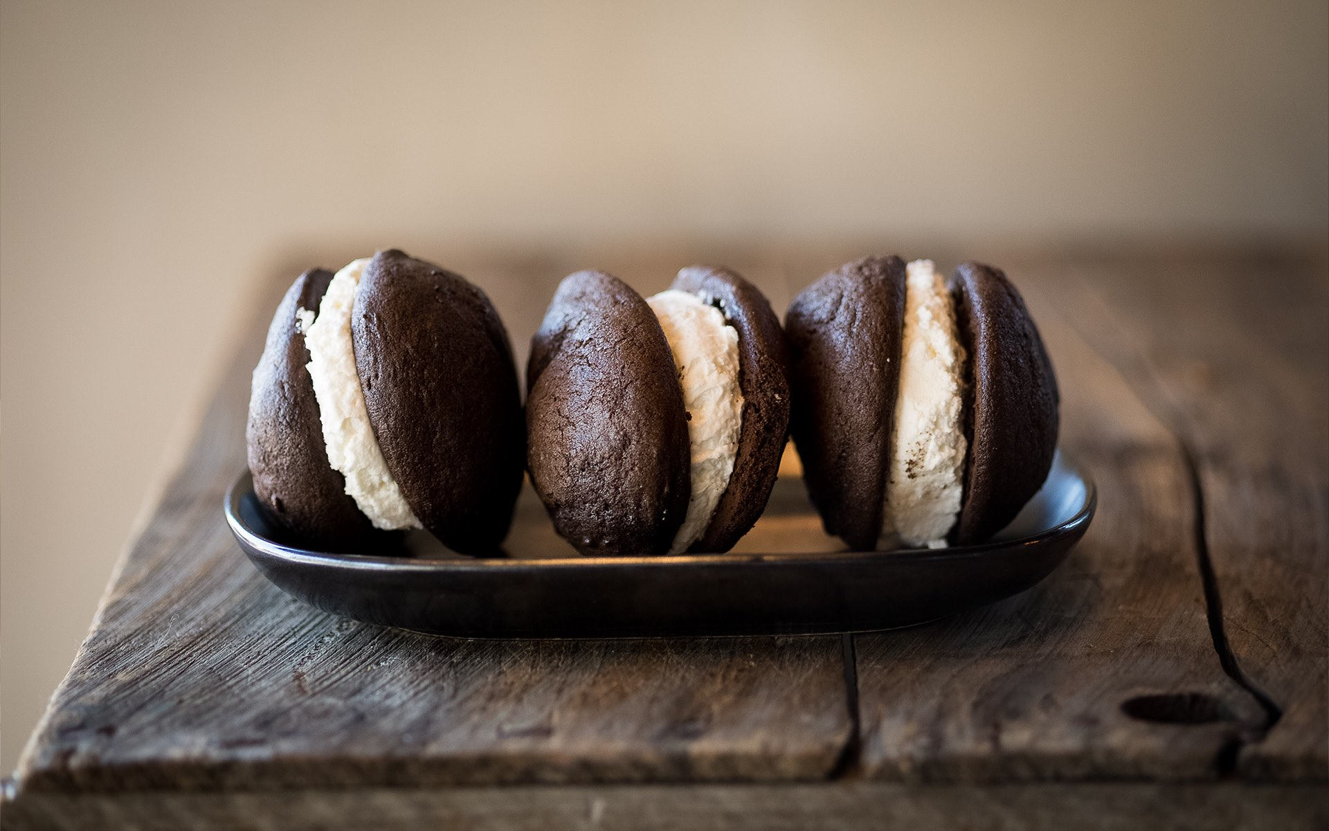 three chocolate dessert sandwiches with cream between them