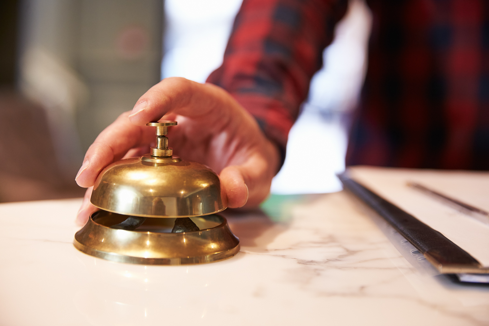 Close up of hand ready to ring desk bell