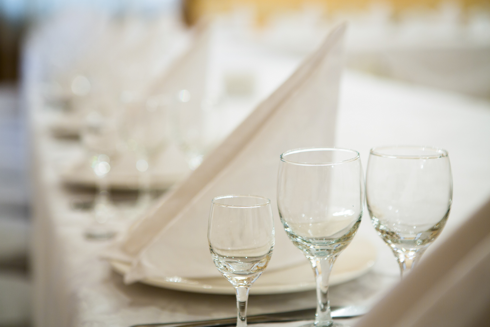 Fancy dining table set with white napkins, plates & crystal glasses