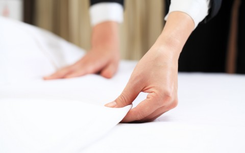 Close up of hands making bed