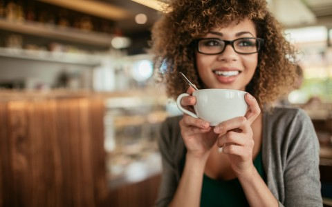 Woman holding teacup with coffee