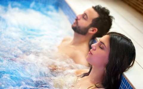 Couple sitting with eyes closed in hot tub