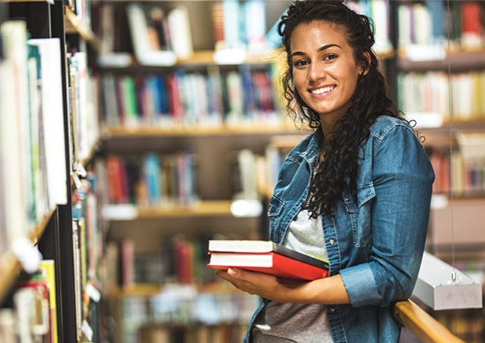 girl in library holding books and smiling