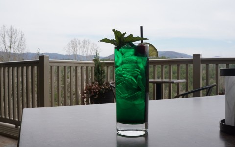 green drink overlooking mountains