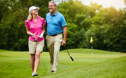 woman and man walking on a golf course