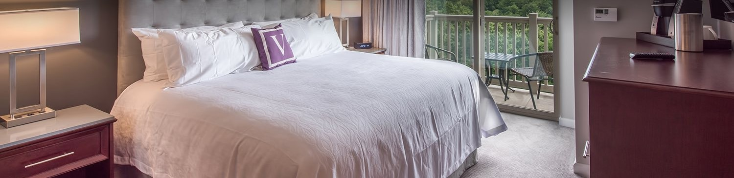 white bedspread with a V purple pillow