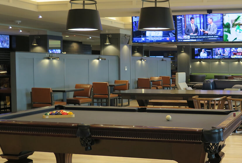 Billiard table next to tvs on ceiling