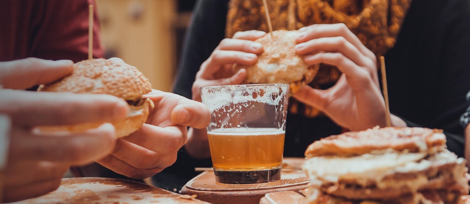Close up of beer and people eating burgers