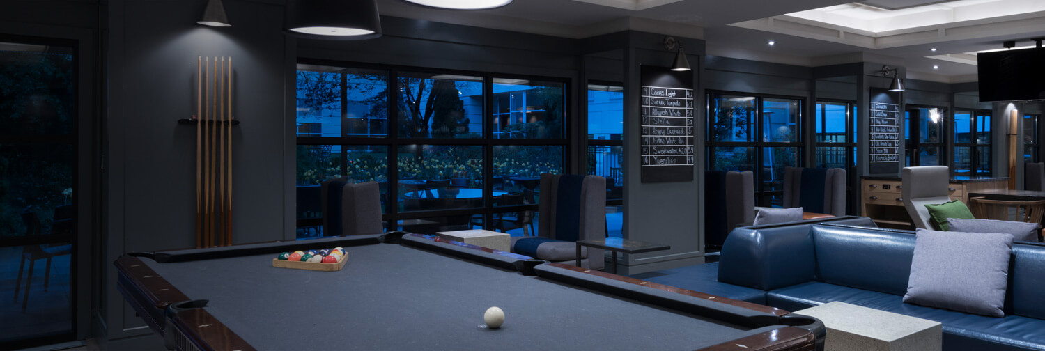 Billiard table with pool sticks on wall