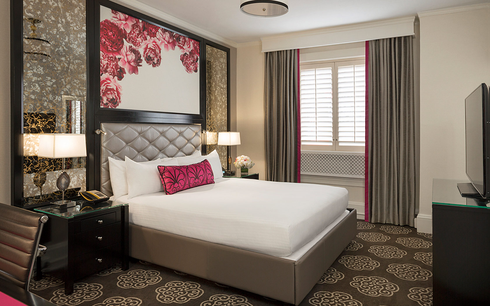queen bed with grey and pink accented curtains and decor