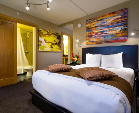 a colorful guestroom with artwork above the bed