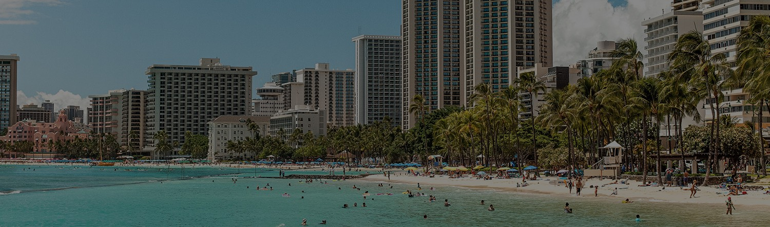people at the beach with waikiki buildings in the background