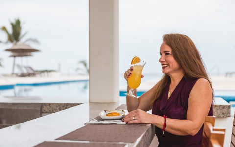 woman drinking cocktail in casadelfin pool view bar