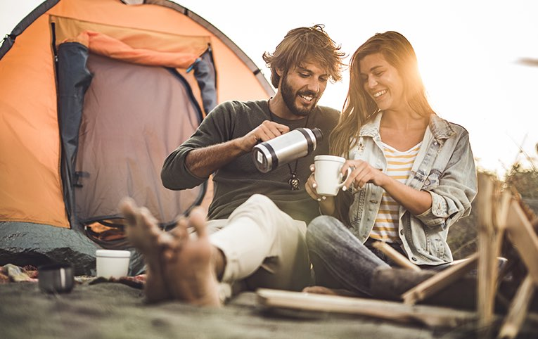 man and woman drinking coffee in front of a tent
