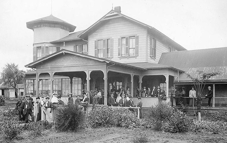 black and white photo of house and group of people on front porch