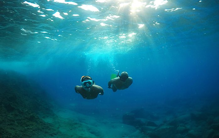 two people snorkeling in blue ocean
