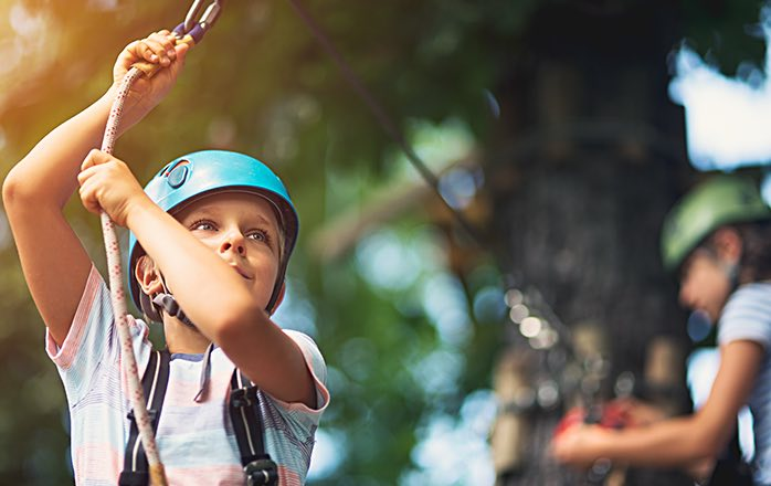 young girl with blue helmet on a zipline