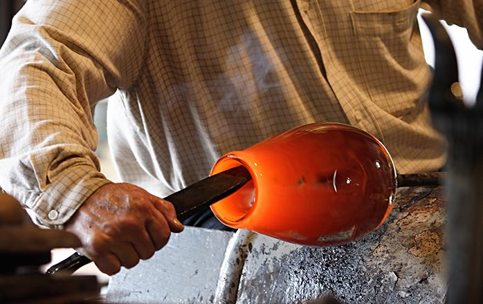 man working glass as its heated into a vase