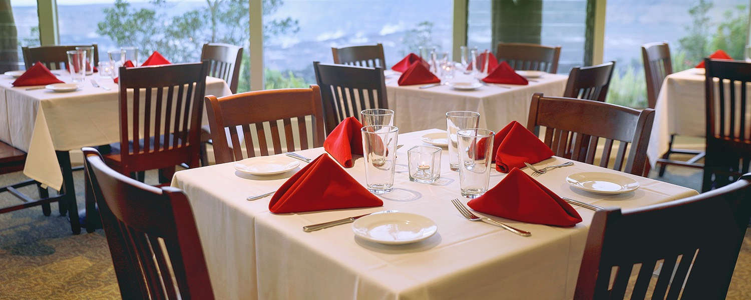 square tables with white tablecloths and red napkins
