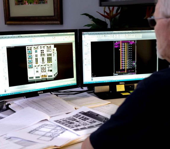 man looking at software on two desktop monitors
