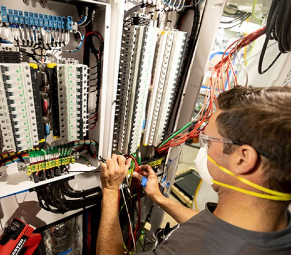 marine engineer repairing an electric panel