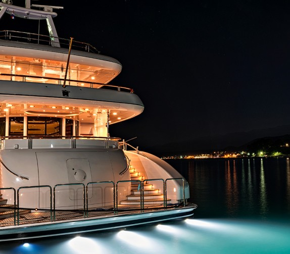 view of a yacht's stern in the water lit up at night