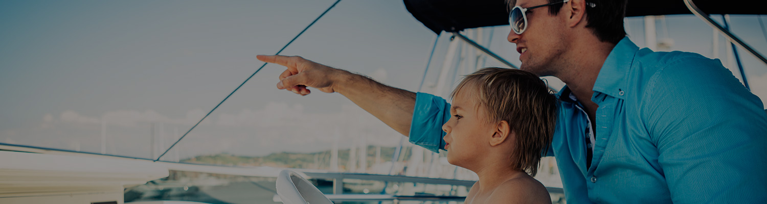 father pointing into the ocean with his son on a boat