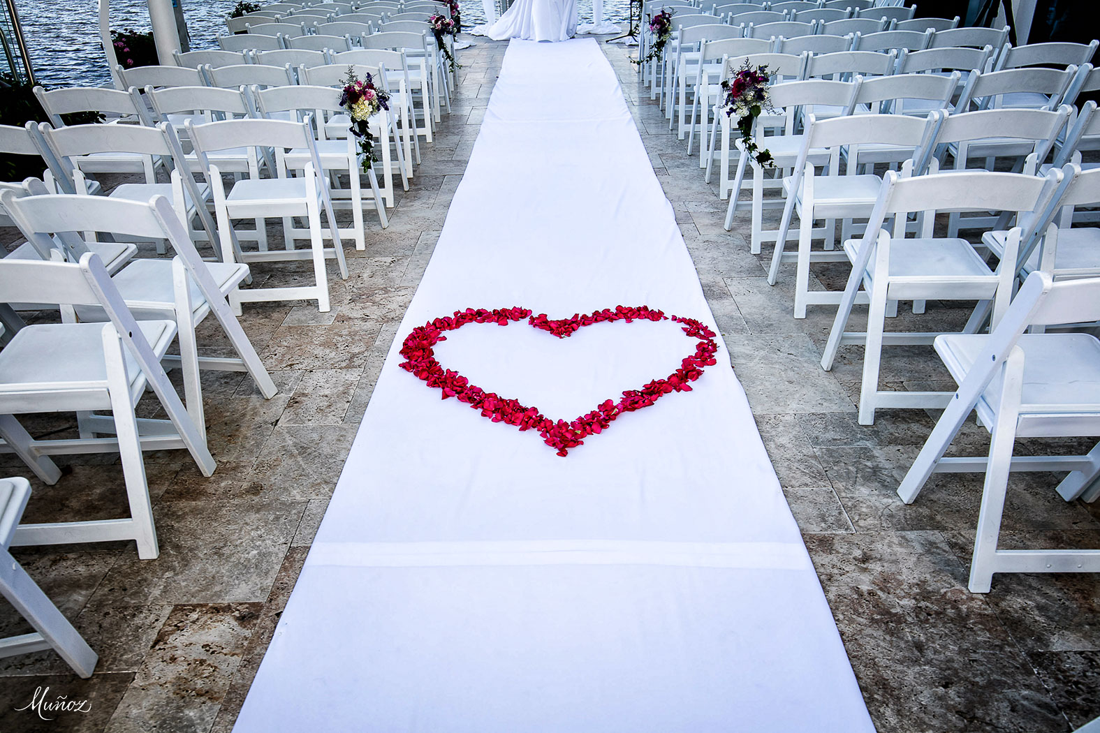Rose petals in heart shape on wedding aisle toward altar