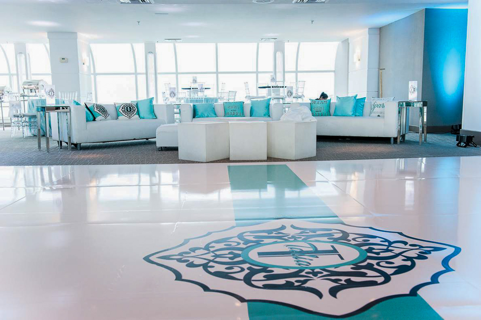 Ballroom with with white tile dance floor and white furniture with blue accents