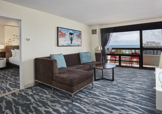 brown couch in suite living room with glass sliding  door leading to intracoastal view