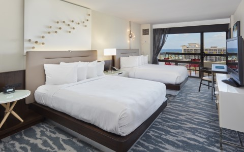 Room with two queen beds and a lit lamp in between them, window with view facing intracoastal
