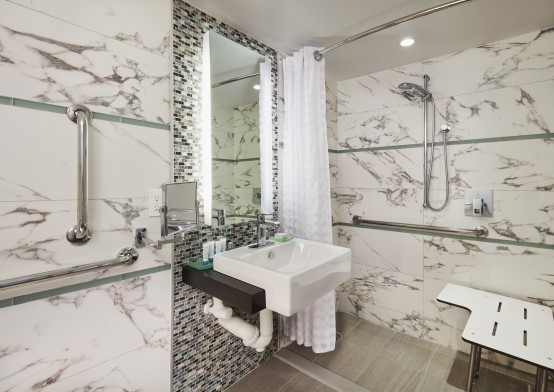 Modern bathroom with white marble walls and shower enclosure, square shallow white sink
