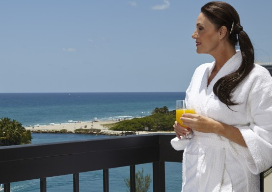 Woman in robe on balcony holding glass of orange juice