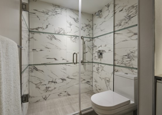 White marble bathroom with toilet and glass shower enclosure
