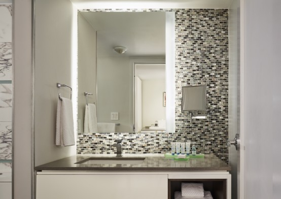 bathroom sink vanity with illuminated mirror and tiled backsplash