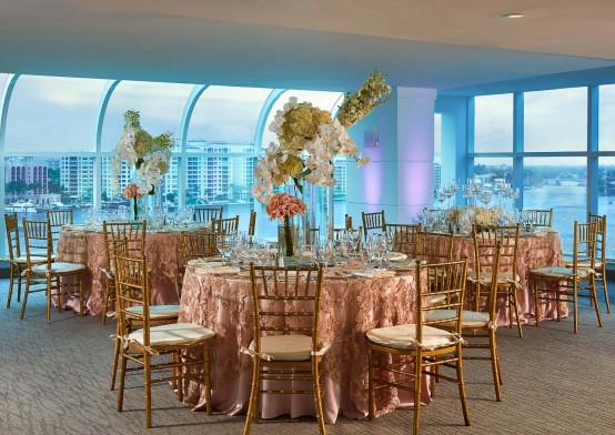 Event room with round tables & floral tablecloths overlooking the ocean