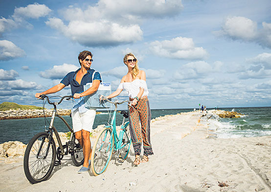 Couple standing next to bikes on beach