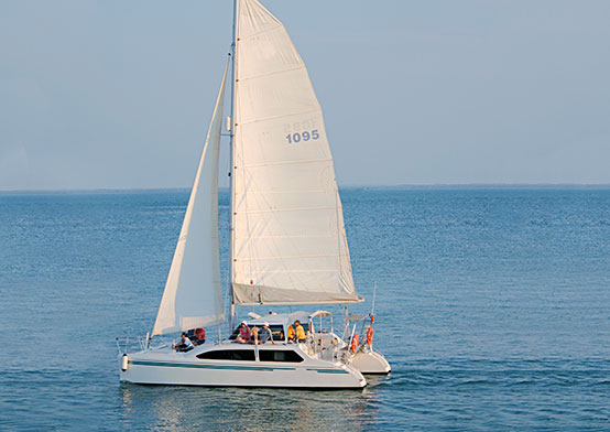 White boat with large white sails in ocean