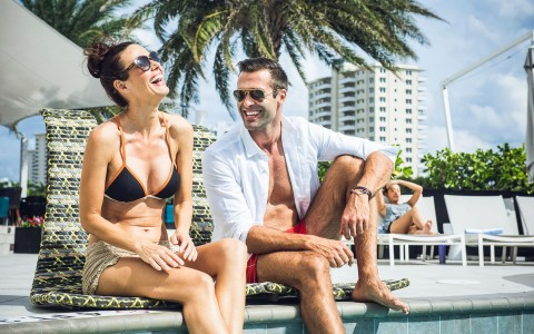 Couple sitting by pool edge laughing
