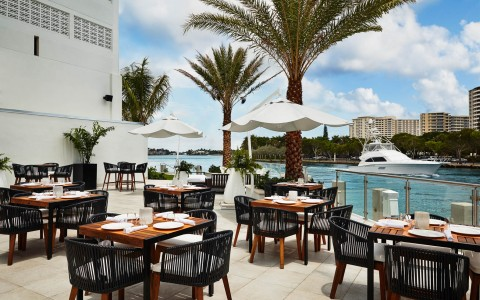 Outdoor dining with square tables & umbrellas next to water