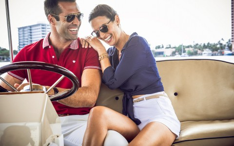 Couple laughing as they drive a boat