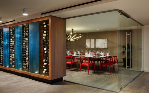 Wall of exposed wines outlining dining area