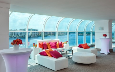 Lounging area with white couches, vibrant pillows & huge water view